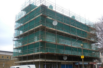 A scaffold pedestrian protection fan erected above local business shops that were still functioning due to the protection fan.