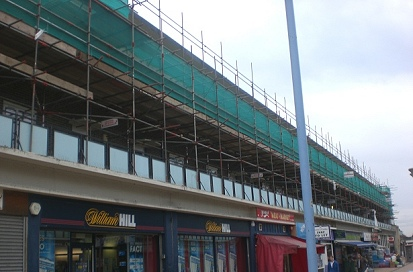 Debris netted independent scaffold at a parade of shops in Thurrock.